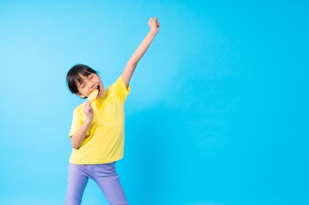 Jong aziatisch meisjesijs eten en ijs die grappig op blauw posten