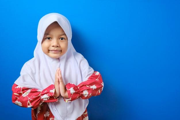 Jong aziatisch moslimmeisje dat hijab-gebaar draagt bij het begroeten en verwelkomen van gast voor eid mubarak Premium Foto