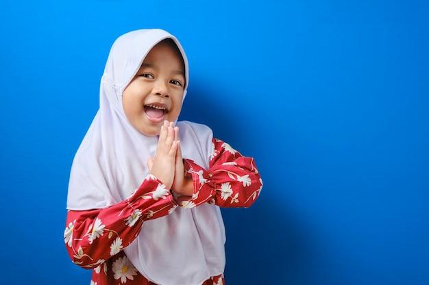 Jong aziatisch moslimmeisje dat hijab-gebaar draagt bij het begroeten en verwelkomen van gast voor eid mubarak