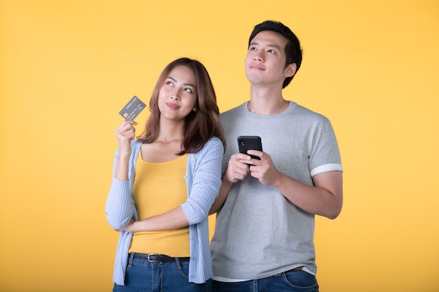 Jong aziatisch paar dat creditcard en smartphone houdt terwijl het kijken omhoog geïsoleerd op gele muur
