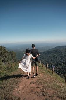 Jong aziatisch paar dat en bovenop heuvel op vakantie omhelst loopt