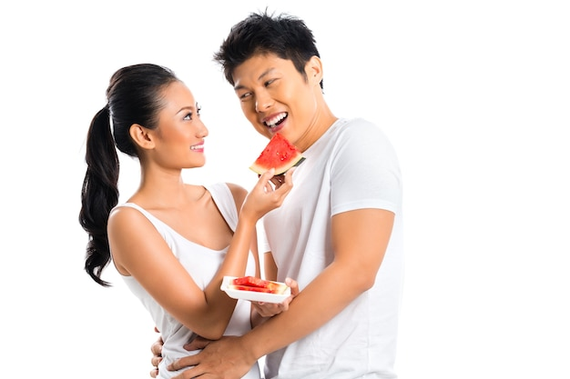 Jong aziatisch paar dat fruit eet en pret heeft
