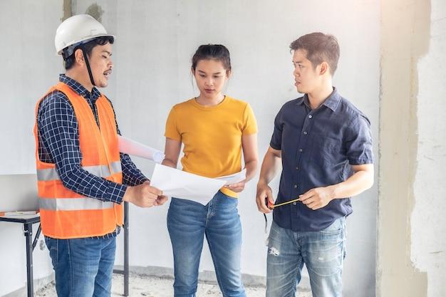 Jong aziatisch paar dat huis controleert met de huisinspectie van de voormantechniek het bouwen van huisklanten