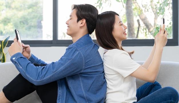 Jong aziatisch paar dat met hun rug op elkaar zit en de telefoon op de bank gebruikt