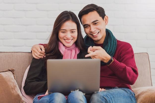 Jong aziatisch paar dat online met laptop winkelt