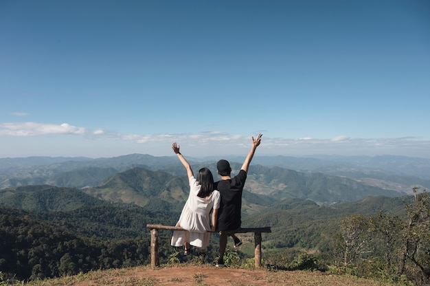Jong aziatisch paar dat opgeheven wapens bovenop heuvel zit