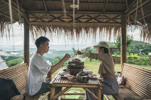 Jong aziatisch paar dat thaise varkensvleesbarbecue eet en grilt op pan in de hut, samen met uitzicht op mist op heuvel op het platteland