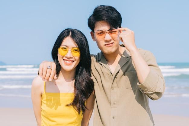 Jong aziatisch paar dat van de zomervakantie geniet op het strand