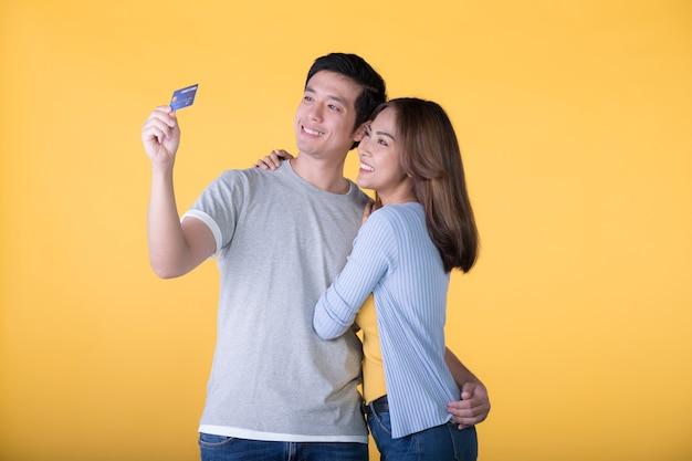 Jong aziatisch paar met creditcard die op gele muur wordt geïsoleerd