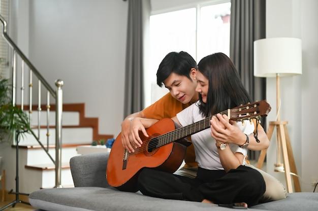 Jong aziatisch paar speelt gitaar en zingt samen een lied op de bank.