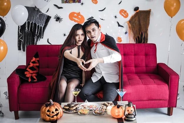 Jong aziatisch stel in kostuumheks en dracula met halloween-feest vieren en je handen in het hart leggen in halloween-festival op rode bank in de kamer thuis.