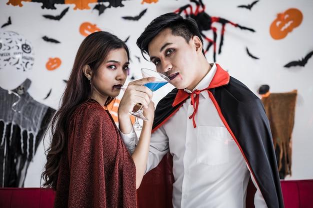 Jong aziatisch stel in kostuumheks en dracula met halloween-feest vieren en samen wijn drinken op halloween-festival in de kamer thuis. concept paar vieren halloween samen thuis.