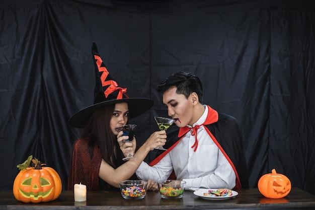 Jong aziatisch stel in kostuumheks en dracula met halloween-feest voor gerinkelglas en drankje op halloween-festival. paar in kostuum vieren halloween-feest zwarte doek achtergrond.