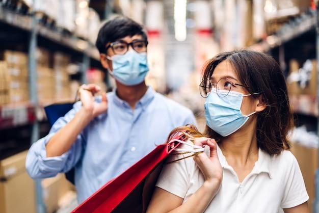 Jong aziatisch stel in quarantaine voor coronavirus met chirurgisch masker gezichtsbescherming met sociale afstand en boodschappentas in de winkel. covid19 en nieuw normaal concept