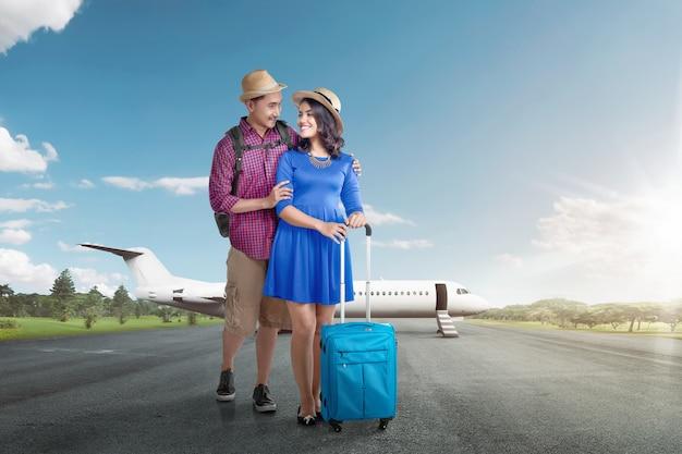 Jong aziatisch toeristenpaar met bagage die reizend met vliegtuig gaan