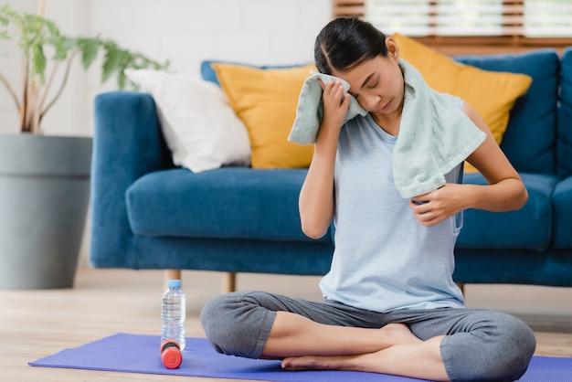 Jong aziatisch vrouwen drinkwater omdat uitgeput rust na oefening in woonkamer voel