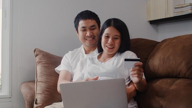 Jong aziatisch zwanger paar dat online thuis winkelt. mamma en papa die gelukkig thuis het gebruiken van laptop technologie en creditcard het kopen babyproduct voelen terwijl thuis het liggen op bank in woonkamer.