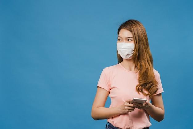 Jong azië-meisje dat een medisch gezichtsmasker draagt met behulp van een mobiele telefoon met gekleed in vrijetijdskleding geïsoleerd op een blauwe muur