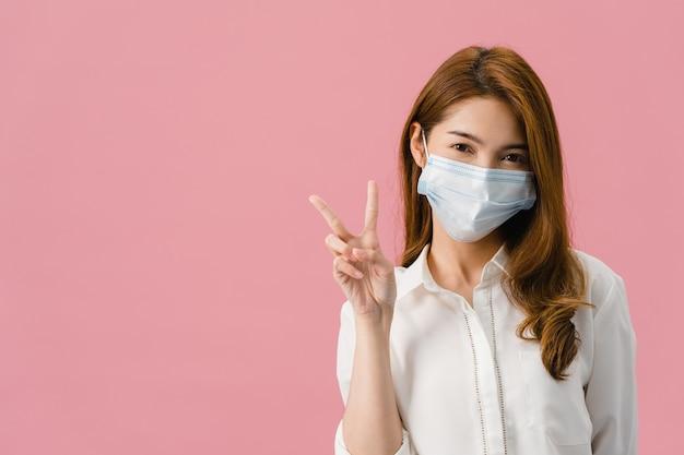 Jong azië-meisje dat medisch gezichtsmasker draagt dat vredesteken toont, aanmoedigt met gekleed in casual doek en kijkt naar camera geïsoleerd op roze achtergrond.