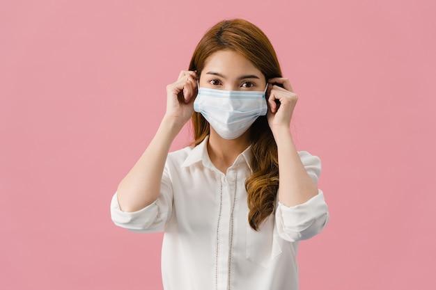 Jong azië-meisje dat medisch gezichtsmasker draagt met gekleed in casual kleding en kijkt naar camera geïsoleerd op roze achtergrond.