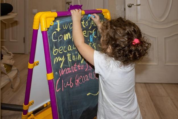 Jong babymeisje schrijft met krijt op bord