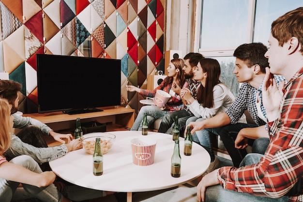 Jong bedrijf kijkt tv-programma's op feestje