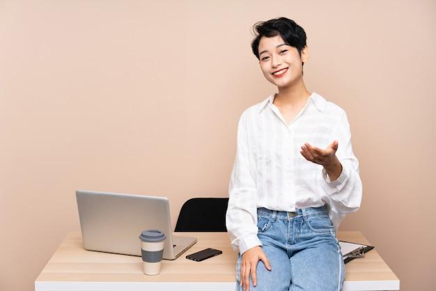Jong bedrijfs aziatisch meisje in haar werkplaatshandenschudden na goede deal