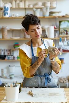 Jong beeldhouwermeisje houdt een pot in de vorm van een spons vast in een pottenbakkerij, student leert werken met ruwe klei