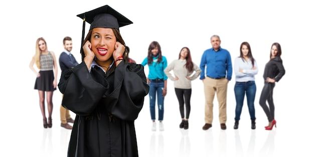 Jong behaalde een diploma zwarte die vlechten dragen die oren behandelen met handen