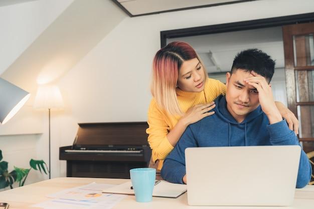 Jong beklemtoonde aziatisch paar die financiën beheren, die hun bankrekeningen herzien gebruikend laptop computer