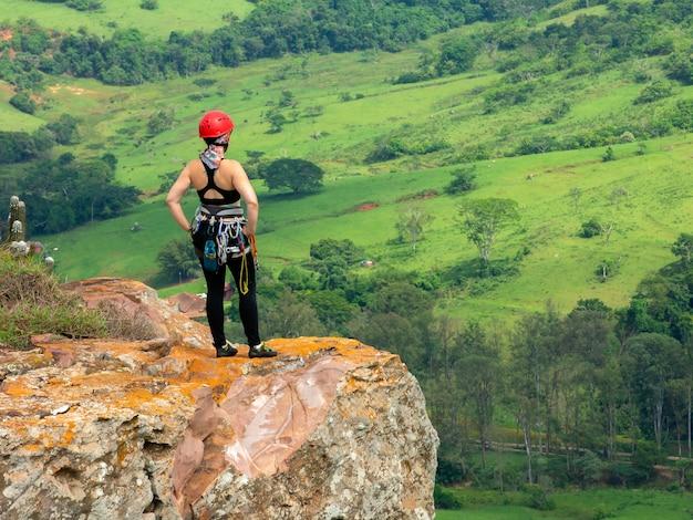 Jong bergbeklimmermeisje die van mening van bergtop genieten na bergbeklimming op zandsteenberg
