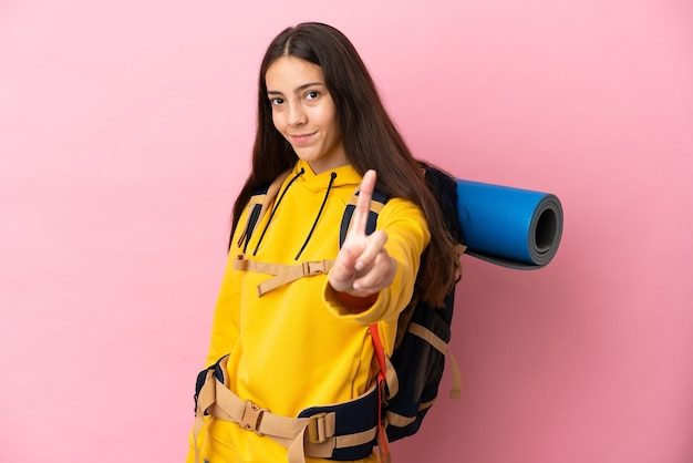 Jong bergbeklimmermeisje met een grote rugzak die op roze achtergrond wordt geïsoleerd die een vinger toont en opheft