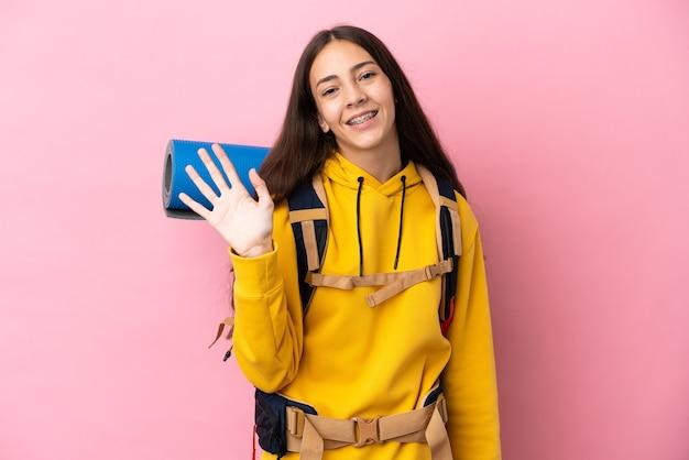 Jong bergbeklimmermeisje met een grote rugzak die op roze achtergrond wordt geïsoleerd die met hand met gelukkige uitdrukking groeten