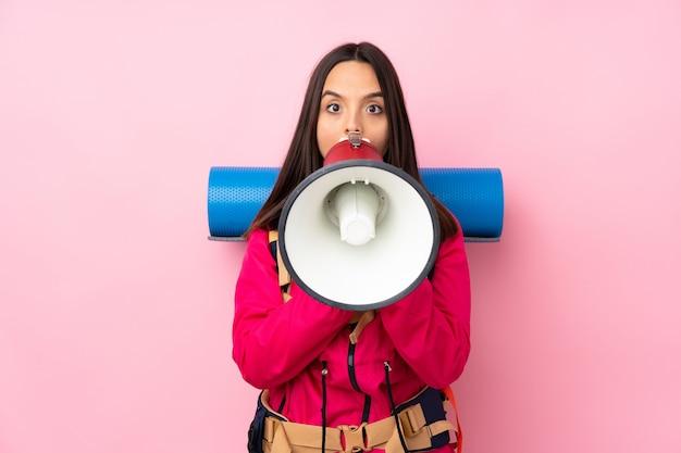 Jong bergbeklimmermeisje met een grote rugzak die over roze door een megafoon schreeuwt