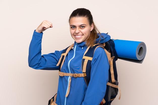 Jong bergbeklimmermeisje met een grote rugzak die sterk gebaar maakt