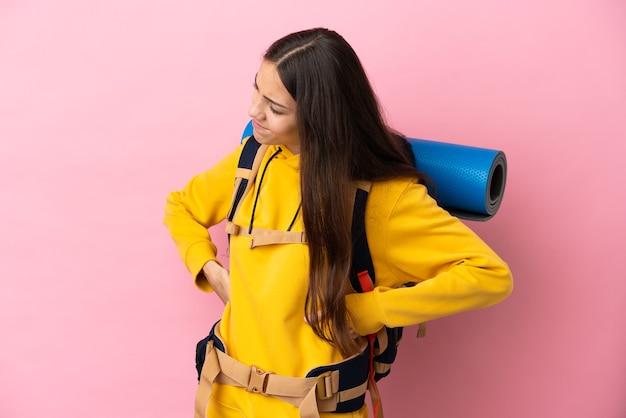 Jong bergbeklimmermeisje met een grote rugzak geïsoleerd die lijdt aan rugpijn omdat ze moeite heeft gedaan