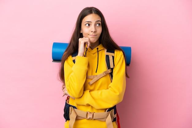 Jong bergbeklimmermeisje met een grote rugzak geïsoleerd die twijfels heeft en denkt