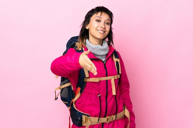 Jong bergbeklimmermeisje met een grote rugzak over geïsoleerd roze handenschudden na veel