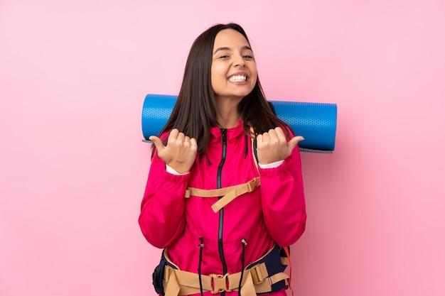 Jong bergbeklimmermeisje met een grote rugzak over roze met duimen op gebaar en het glimlachen