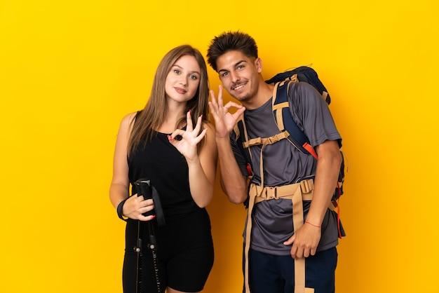 Jong bergbeklimmerpaar met een grote rugzak op geel die een ok teken met vingers toont