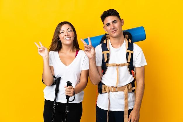 Jong bergbeklimmerpaar met een grote rugzak op geel die en overwinningsteken glimlachen toont