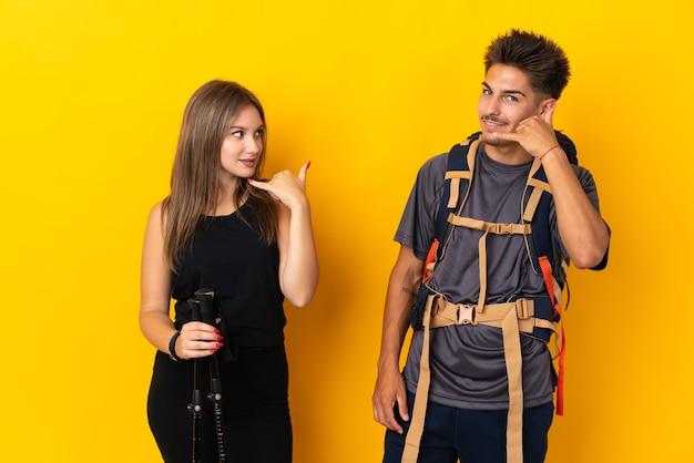 Jong bergbeklimmerpaar met een grote rugzak op geel die telefoongebaar maken. bel me terug teken