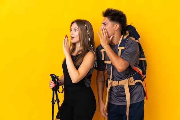 Jong bergbeklimmerpaar met een grote rugzak op geel schreeuwen met wijd open mond naar lateraal