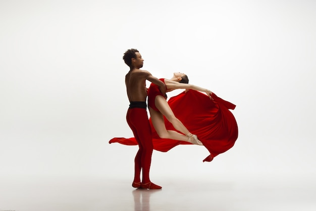 Jong bevallig paar balletdansers die op witte studioachtergrond dansen