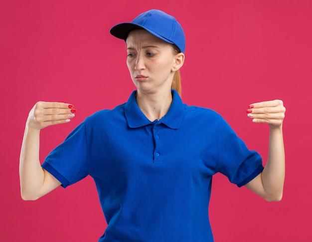 Jong bezorgmeisje in blauw uniform en pet die zelfverzekerd gebarend met handen kijkt alsof je iets vasthoudt dat over een roze muur staat