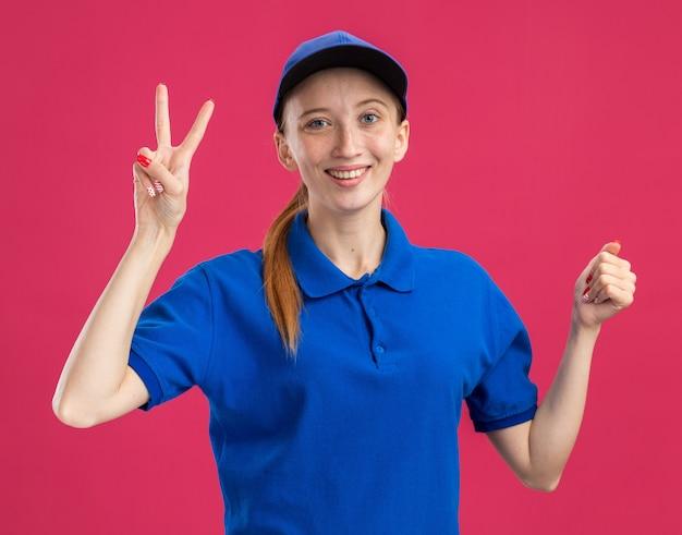 Jong bezorgmeisje in blauw uniform en pet glimlachend vriendelijk met v-teken en gebalde vuist die over roze muur staat
