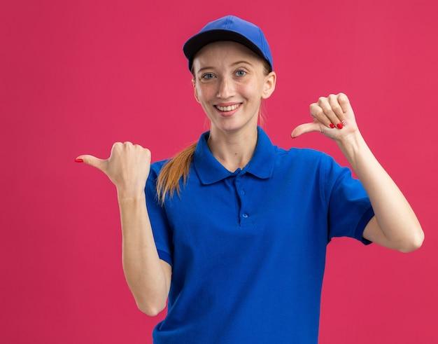 Jong bezorgmeisje in blauw uniform en pet glimlachend zelfverzekerd wijzend met duimen naar de zijkant die over roze muur staat