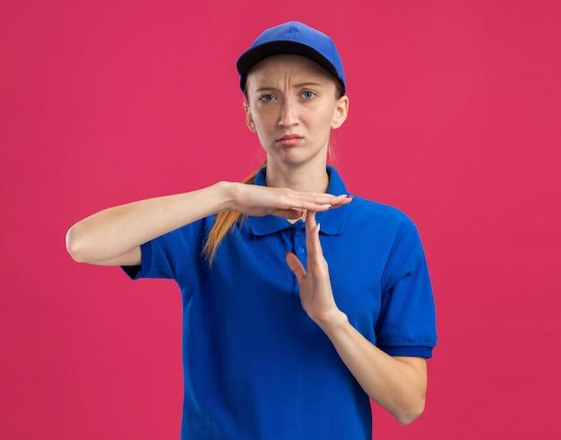 Jong bezorgmeisje in blauw uniform en pet met een serieus gezicht dat een time-outgebaar maakt met handen die over een roze muur staan