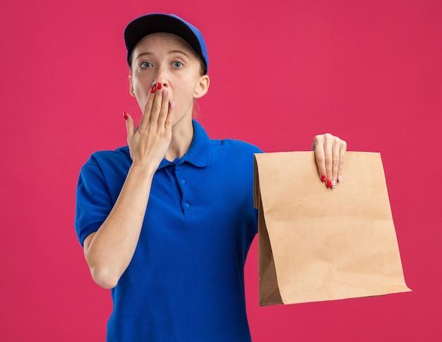 Jong bezorgmeisje in blauw uniform en pet met papieren pakket dat geschokt is en mond bedekt met hand die over roze muur staat