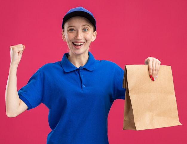 Jong bezorgmeisje in blauw uniform en pet met papieren pakketje blij en opgewonden, gebalde vuist over roze muur